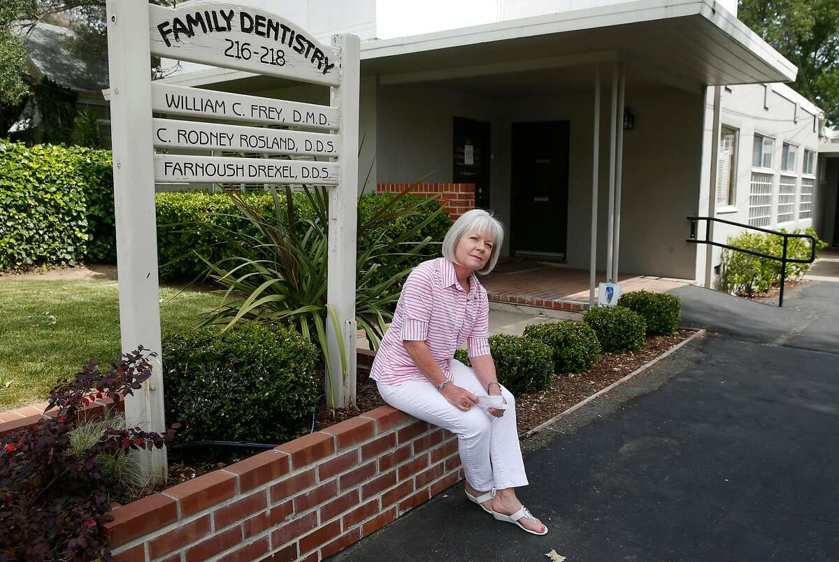 Cathy Oleson is seen outside of the dental office where she's worked as a hygenist for the past 25 years in Los Gatos, Calif. on Wednesday, April 29, 2020. Oleson is temporarily out of work as the coronavirus pandemic continues.