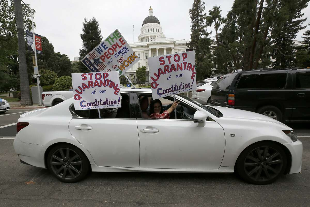 A car carrying protesters calling for the end Gov Gavin Newsom's stay-at-home orders passes the state Capitol in Sacramento, Calif., Monday, April 20, 2020. Several hundred people gathered at the Capitol calling for Newsom to ease the restrictions and allow people return to work.(AP Photo/Rich Pedroncelli,)