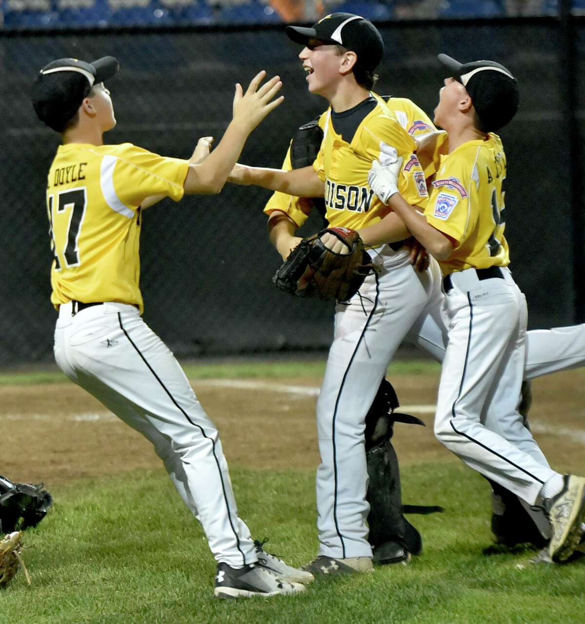 Bristol, Connecticut - Tuesday, August 6, 2019: Teammates cheer with Johnny Reh, third from left, after he pitched the last strike celebrating a Connecticut Madison Little League of Madison, CT win over Walpole Little League of Walpole, MA Tuesday at the Giamatti Little League Center in Bristol during the 2019 Little League Baseball Eastern Regional Tournament. Madison, CT defeated Walpole, MA 4-1