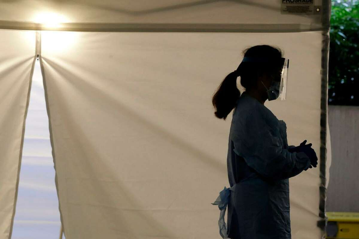 In this March 13, 2020, file photo, a nurse at a drive-up coronavirus testing station wears a face shield and other protective gear as she waits by a tent in Seattle. President Donald Trump has hinted that he might extend a 60-day hold on green cards that he has ordered to protect American jobs during the coronavirus pandemic.