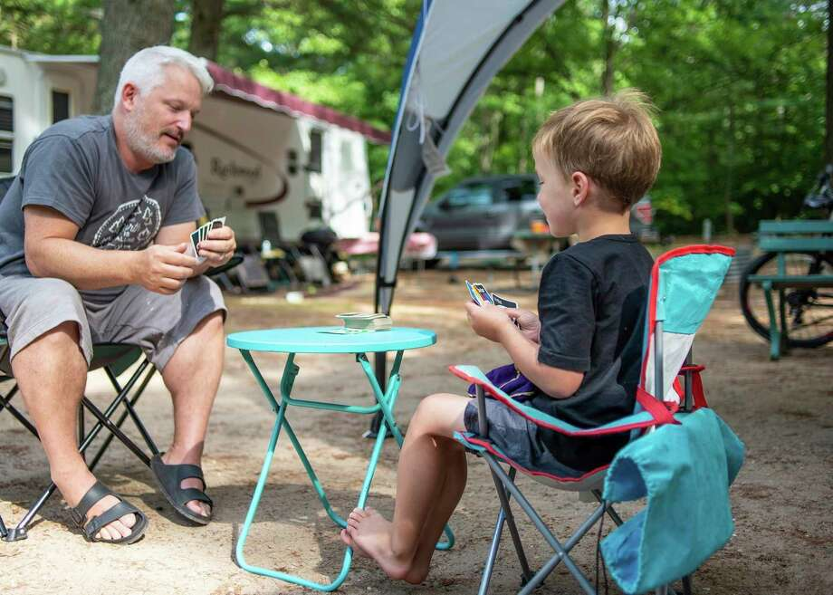A family plays cards at Interlochen State Park. The Department of Natural Resources has updated expected opening dates and available amenities at many of its public outdoor recreation sites and facilities. (Courtesy photo) / © 2019 State of Michigan