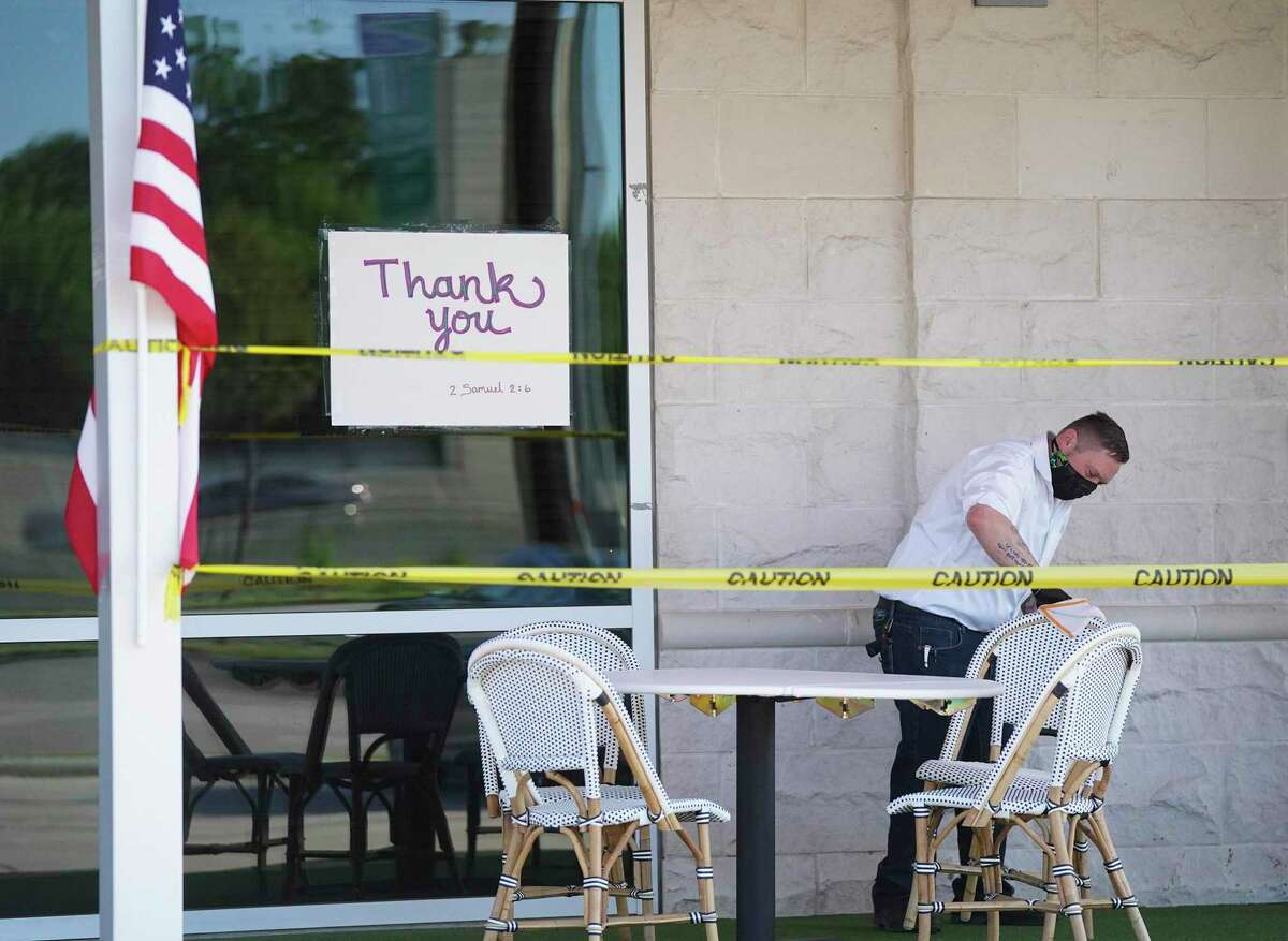 A Federal American Grill employee wipes down chairs after some sat in them outside the Hedwig Village restaurant on Friday, April 24. Federal American opened one week before the governor allowed all restaurants to do so.