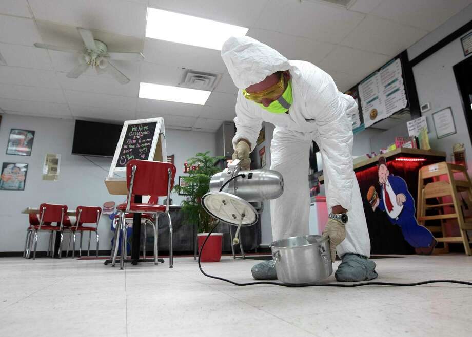 As businesses opened doors Friday, the county recorded two more COVID-19 deaths for a total of 14. An employee with ProTech Disinfect uses a mist cleaning solution to deep clean the kitchen, seating area, restaurant and other spaces at Burger Fresh. Photo: Jason Fochtman, Houston Chronicle / Staff Photographer / 2020 © Houston Chronicle