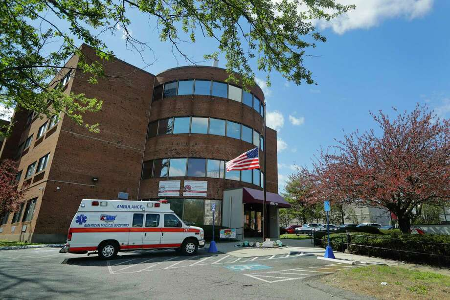 An ambulance used to transport a patient is parked outside the Northbridge Health Care Center Wednesday, April 22, 2020, in Bridgeport, Conn. To slow the spread of the coronavirus inside nursing homes, Connecticut began transferring infected residents to off-site recovery centers following their release from hospitals. Photo: Frank Franklin II / Associated Press / Copyright 2020 The Associated Press. All rights reserved.