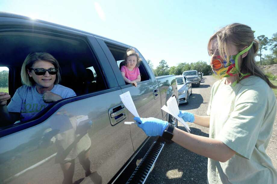 Sarah Yashinskie talks with Melanie Wright as she picks up thier order on Thursday's drive-thru farmstand at Donna's Farm. The organic farm also gets produce and other farm fresh foods from fellow farmers in a co-op style collaboration to offer a variety of fresh and organically grown food. Since COVID-19 restrictions went into place, Donna's Farm shifted Thursday's on site farm market night to a drive-thru model, and have had over 60 vehicles on average each week.