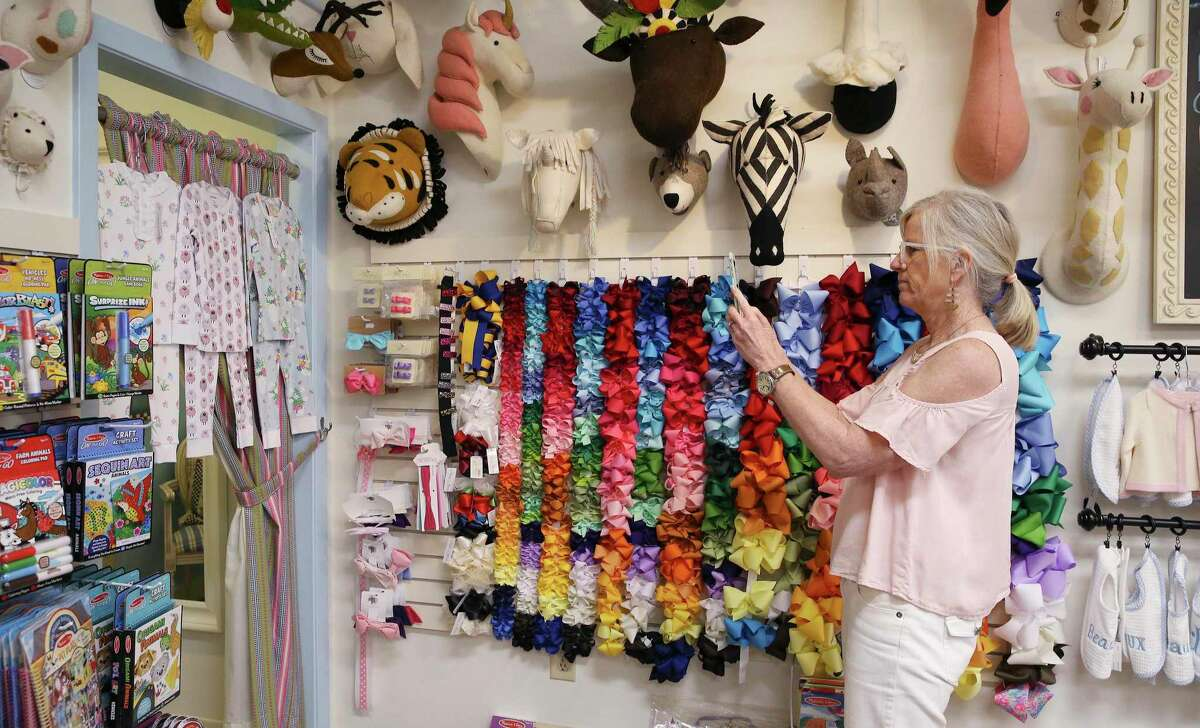 Sheila Jackson takes pictures of children's clothing at Belles & Beaux Children's Boutique to send to a customer who inquired about a purchase by phone.