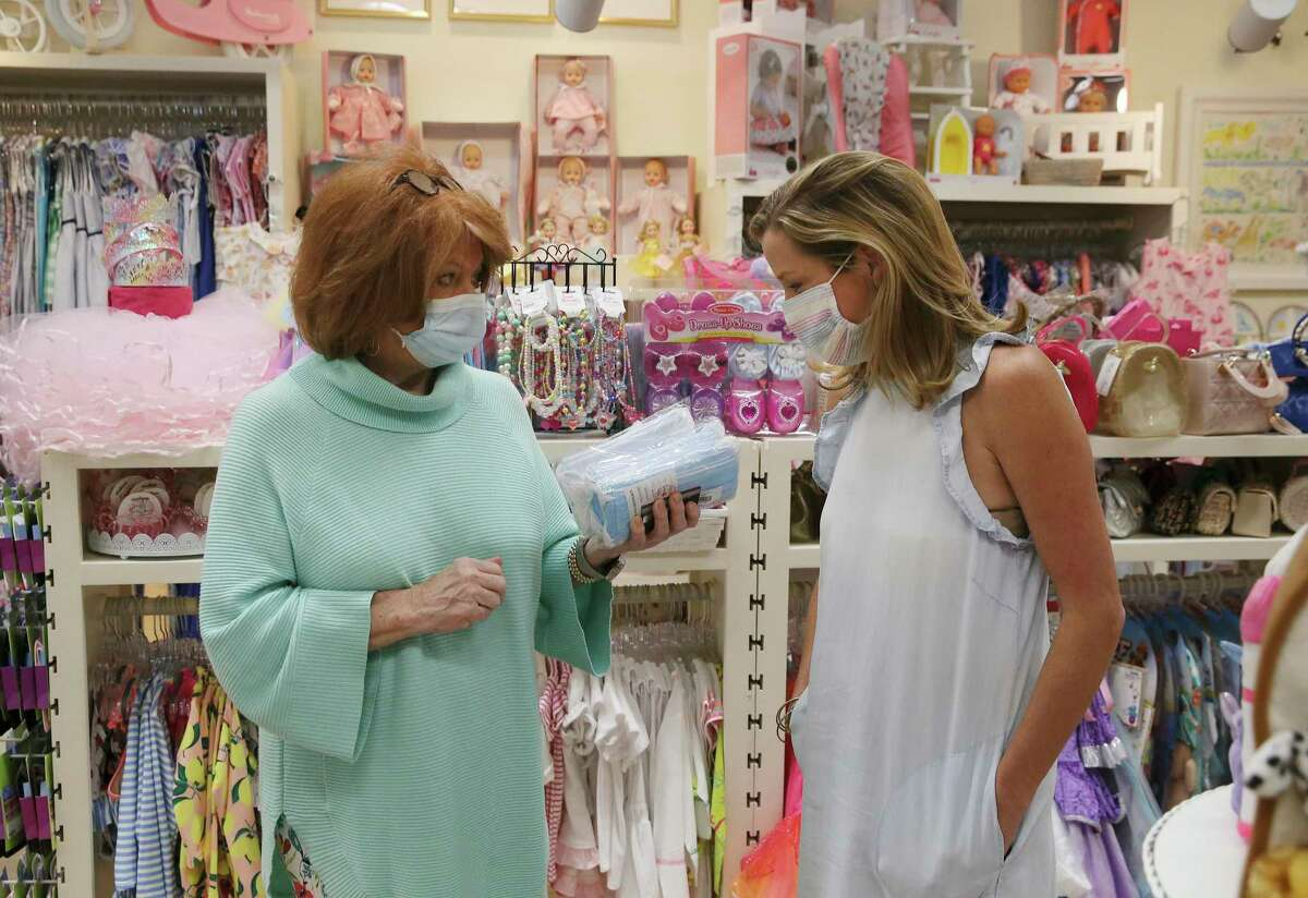 Jan Kirk (left) holds packages of masks to show to Christen Wommack, owner of Belles & Beaux children's boutique, that they may offer to unmasked customers. We think every business should require customers to wear masks.