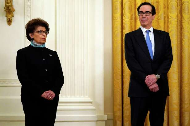 Jovita Carranza, administrator of the Small Business Administration and Treasury Secretary Steven Mnuchin listen as President Donald Trump speaks during a Tuesday event at the White House about the Paycheck Protection Program established to support small businesses during the coronavirus pandemic. Carranza and Mnuchin determined that businesses in bankruptcy would not be eligible for a PPP loan.