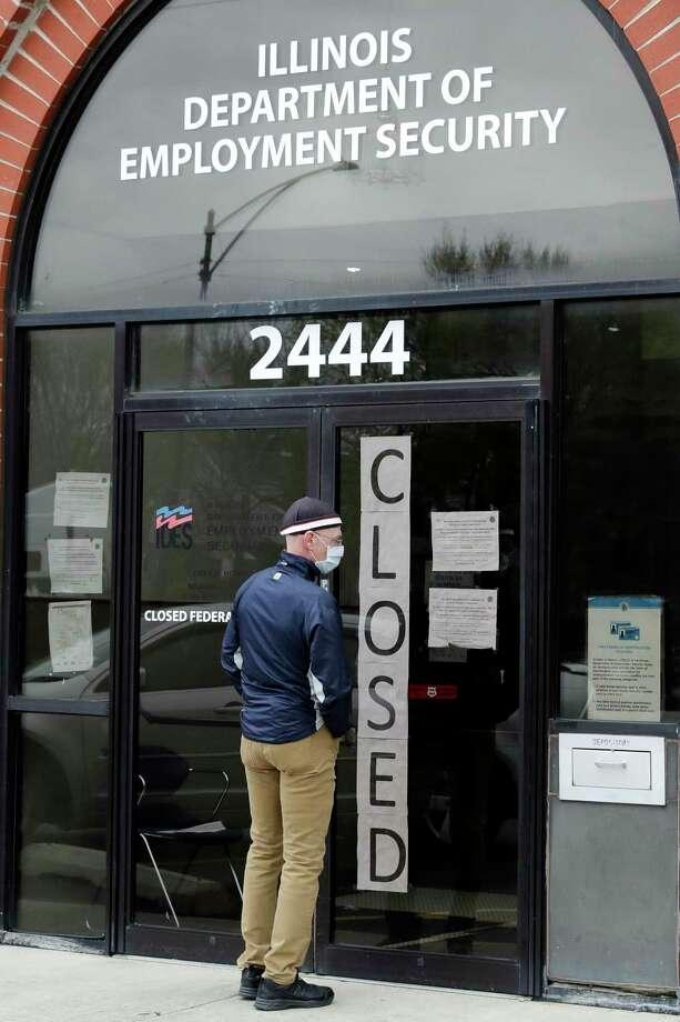 Un hombre lee información enfrente del Departamento de Seguridad del Empleo de Illinois en Chicago, el jueves 30 de abril de 2020. Photo: Nam Y. Huh /Associated Press / Copyright 2020 The Associated Press. All rights reserved.
