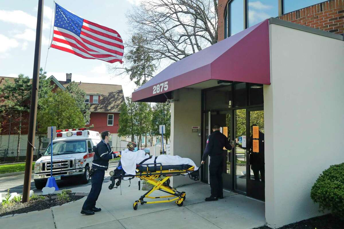 Medical workers bring a patient to the Northbridge Health Care Center Wednesday, April 22, 2020, in Bridgeport. To slow the spread of the coronavirus inside nursing homes, Connecticut has been transferring infected residents to off-site recovery centers following their release from hospitals.