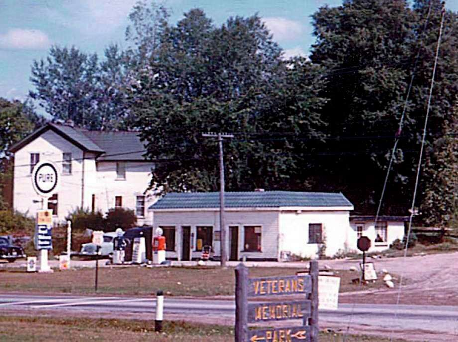 George Pontious sold gas and cut hair at this location on the corner of Smith Street and old U..S-10. Today the Eagles Club is located here. The two-story house in the background was referred to originally as the Murphy house and in later years as the Smith house. Picture is circa late 1950s.