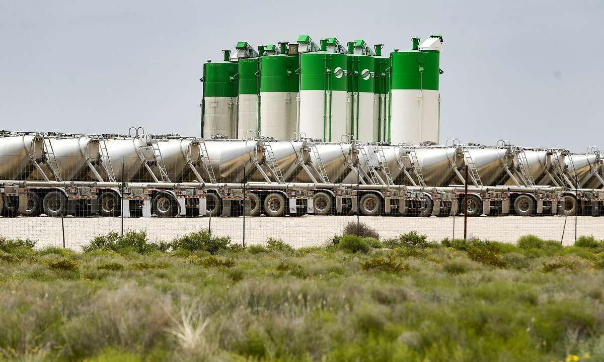 Oil silos and tanker trucks parked at TSS lot near Odessa, Texas on Monday, April 27, 2020.