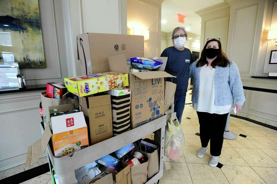 Resident Janice Richman and Danielle Burrows, Community Manager at Park Place, stand next to a cart of food items collected by residents. Residents of 101 Park Place at Harbor Point on Washington Boulevard in Stamford, Connecticut donated non-perishable food items to a local food pantry on Thursday, April 30, 2020. CORT Furniture Rental, a vendor of 101 Park Place delivered the donation to Connecticut Food Bank in Wallingford, who has partnered with Move for Hunger to distribute several local food pantries through out the area. Photo: Matthew Brown / Hearst Connecticut Media / Stamford Advocate