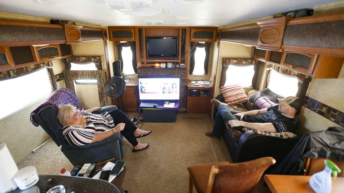 Jana Chapman sits in her trailer with Chris Prevost in Odessa, Texas on April 27, 2020. Prevost still has his job as an operations manager with COT Oilfield Experts, but says he's had to take on more jobs and a pay cut as the company downsizes.