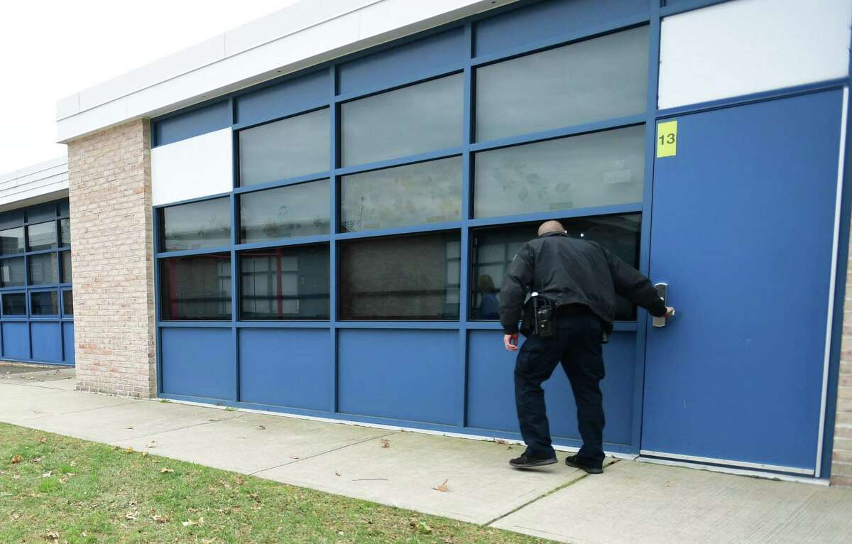 School Resource Officer Neal Robertson and Naramake Elementary School staff work through the school to make sure doors are locked and blinds closed during a drill on Nov. 22, 2019, at the school in Norwalk. In the post-coronavirus world, pandemic drills may become a regular part of school life like lockdowns and shelter-in-place drills.