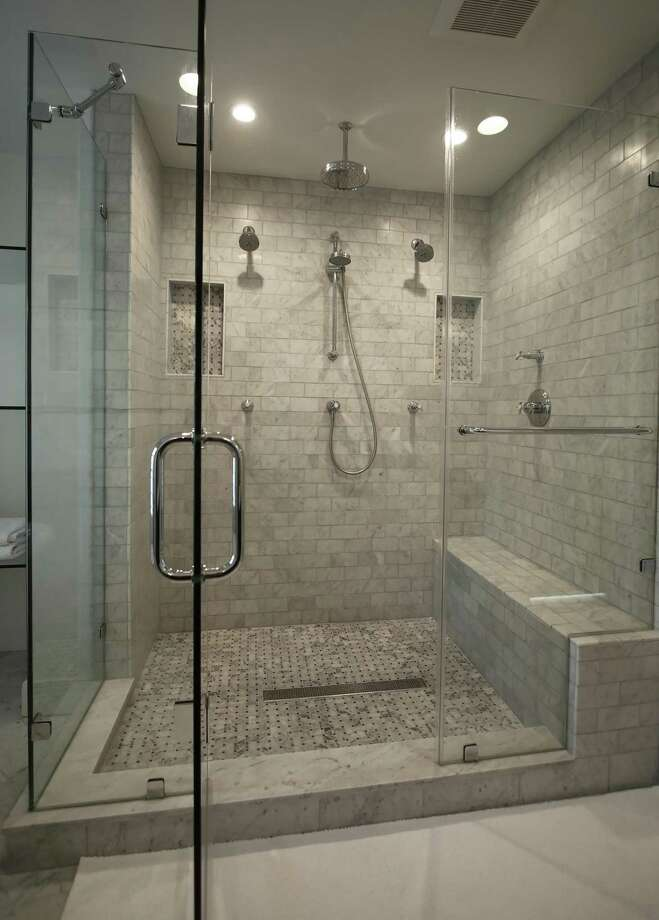 This master bath with frameless glass shower doors has dual showerheads.