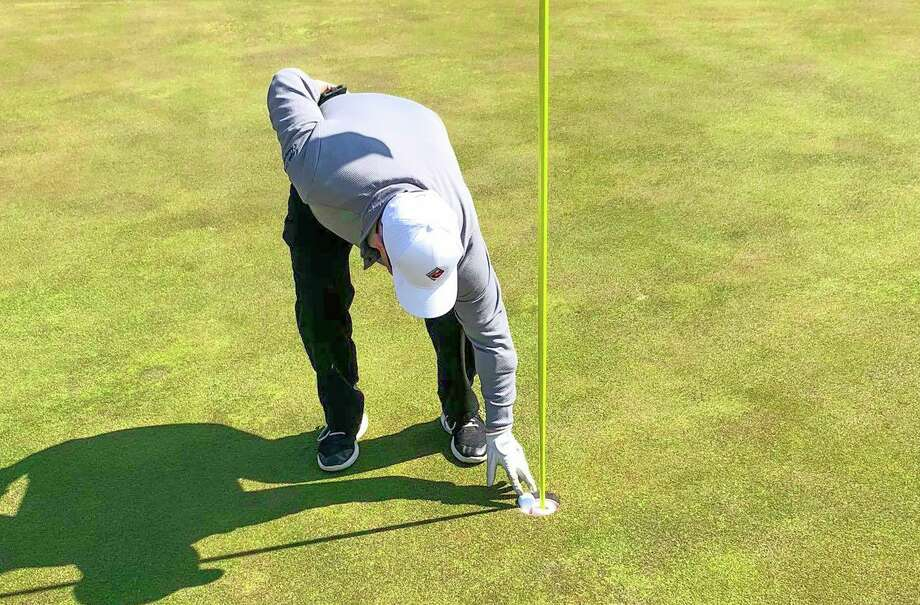 Ron Johnston, of Bad Axe, picks up his ball after recording his first-ever hole-in-one at Verona Hills Golf Club on Tuesday. Golfers have flocked to Thumb-area courses since they reopened on April 24. (Verona Hills Golf Club/Courtesy Photo)