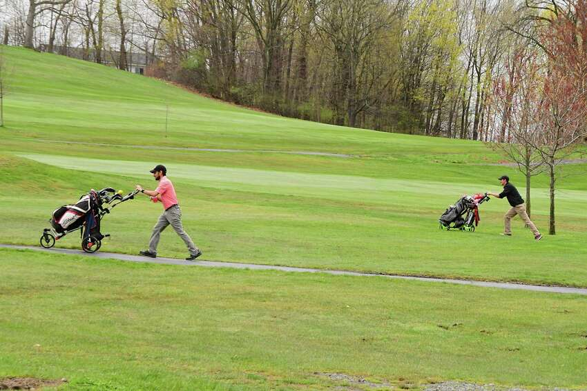 Khach Karayan of Troy, left, and Gary Lennox of Troy practice social distancing as they play a round of golf on opening day at Frear Park Municipal Golf Course Friday, May 1, 2020 in Troy, N.Y. The golfers are required to adhere to social distancing requirements to limit the possible spread of COVID-19. (Lori Van Buren/Times Union)