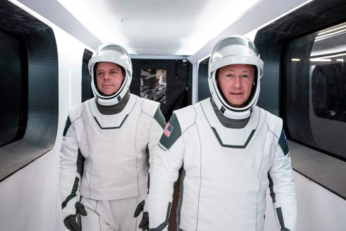 NASA astronauts Bob Behnken, left, and Doug Hurley, wearing SpaceX spacesuits, walk through the Crew Access Arm connecting the launch tower to the SpaceX Crew Dragon spacecraft during a dress rehearsal at NASA's Kennedy Space Center in Florida on Jan. 17, 2020.