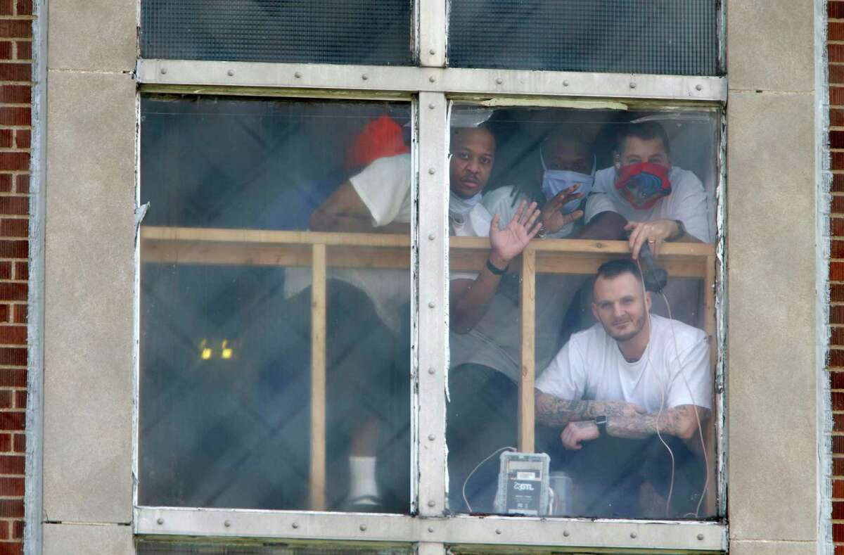 Inmates at the Westville Correctional Facility in Westville, Ind., watch protesters from a window on Tuesday, April 28, 2020. The protesters want better safety measures after an outbreak of COVID-19 cases at the prison. (Kale Wilk/The Times via AP)