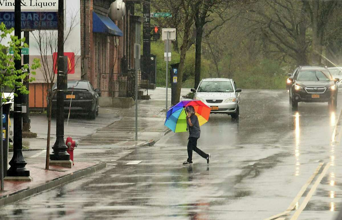 A pedestrian crosses New Scotland Ave. with an umbrella during a steady rain on Friday, May 1, 2020 in Albany, N.Y. Big storms will also move through region on Sunday, June 28, 2020. (Lori Van Buren/Times Union)