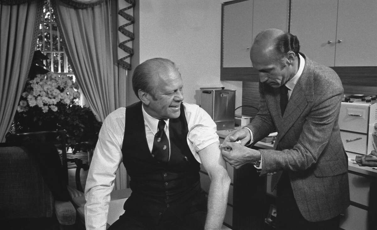 President Gerald Ford receives a swine flu inoculation from his White House physician, William Lukash, in 1976.