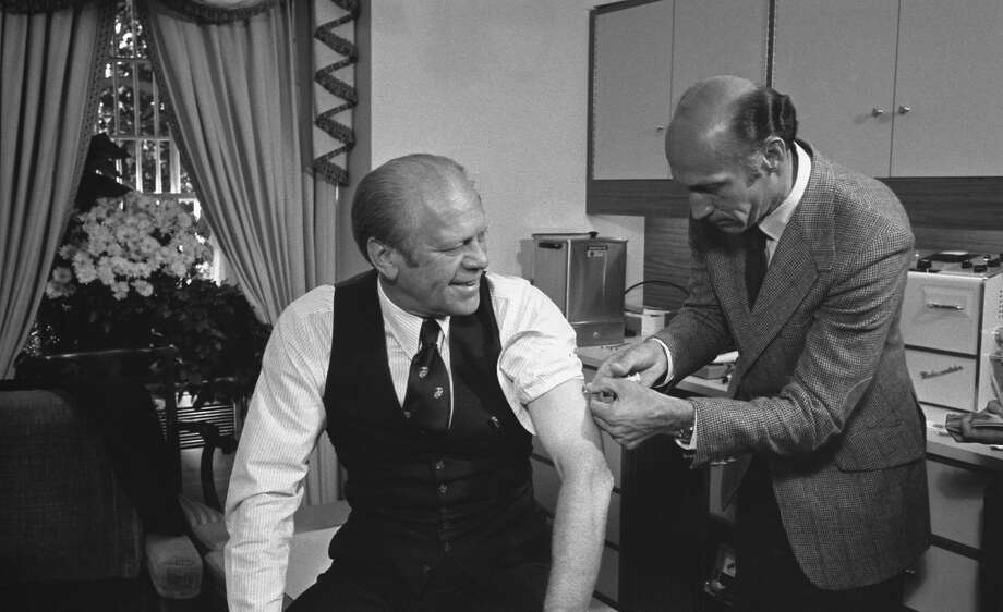 President Gerald Ford receives a swine flu inoculation from his White House physician, William Lukash, in 1976. Photo: David Hume Kennerly/Courtesy Gerald R. Ford Library / The Washington Post