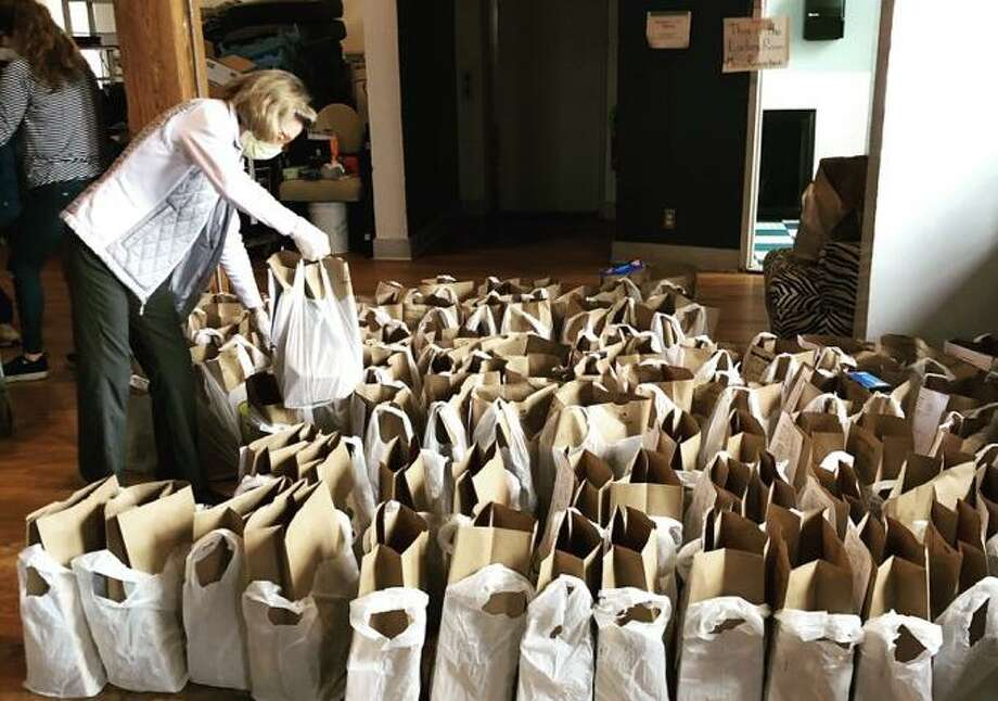 Volunteers prepare food parcels at the Neighbor to Neighbor's temporary location at Arch Street Teen Center. Photo: / Contributed