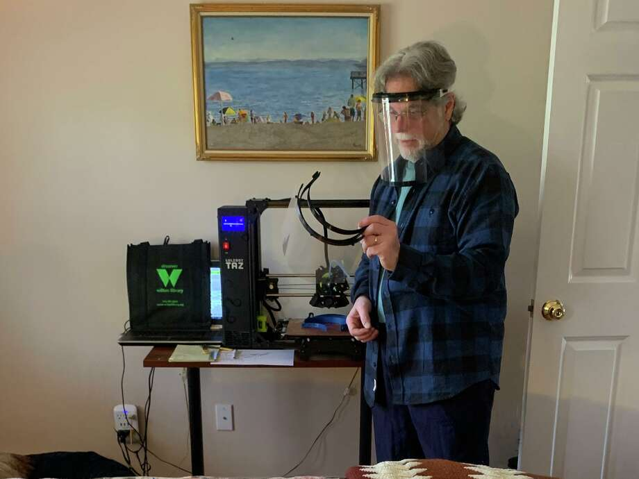 Michael Franco tries on and examines one of the face shields being made with Wilton Library's 3D printer. April 2020 Photo: Contributed Photo / Wilton Library / Wilton Bulletin Contributed