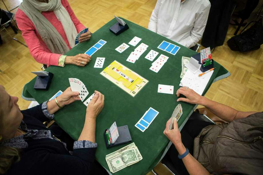 Players check their hands during a weekly bridge game at the Greenwich YWCA that is taught by Steve Becker. The class of about 40 people played on Friday, October 27, 2017. Photo: File / Johnathon Henninger /