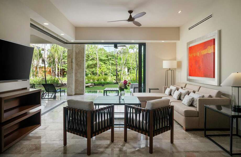Retractable glass walls on two sides of the great room open to a backyard with a private garden and pool. Photo: Fairmont Mayakoba Residences / IONE ASCANIO GREEN