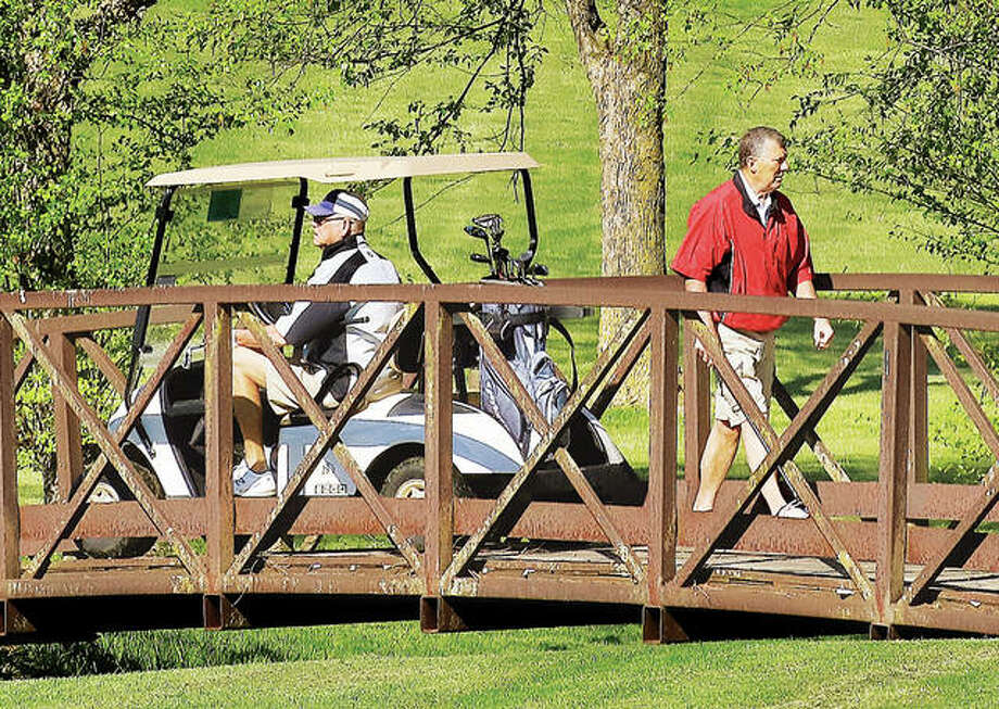Two golfers cross a bridge Friday at the Spencer T. Olin Golf Course in Alton. Friday was the first day golf courses in Illinois were allowed to reopen with restrictions after being closed more than a month because of the COVID-19 pandemic. Photo: John Badman | The Telegraph