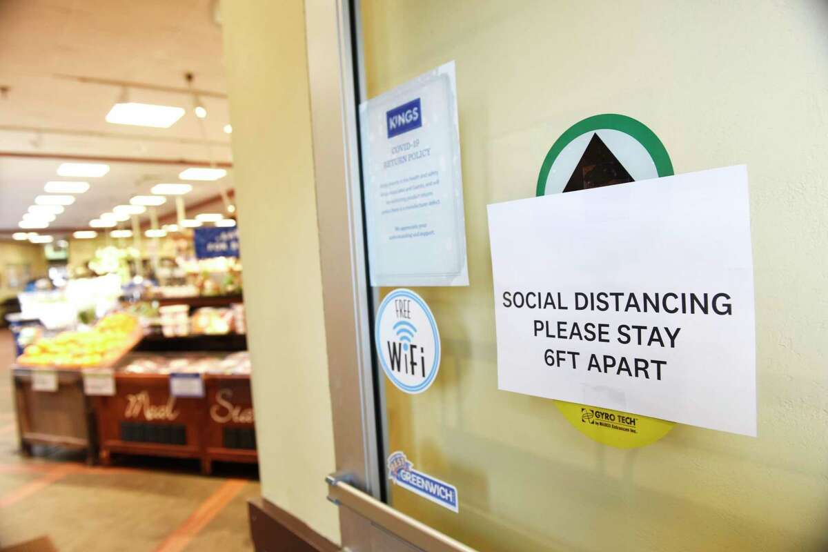 A sign promotes social distancing at the entrance of Kings Food Markets in Old Greenwich, Conn., March 30, 2020. Many grocery stores are taking precautions in preventing the spread of coronavirus including signs promoting social distancing and plexiglass between shoppers and cashiers.