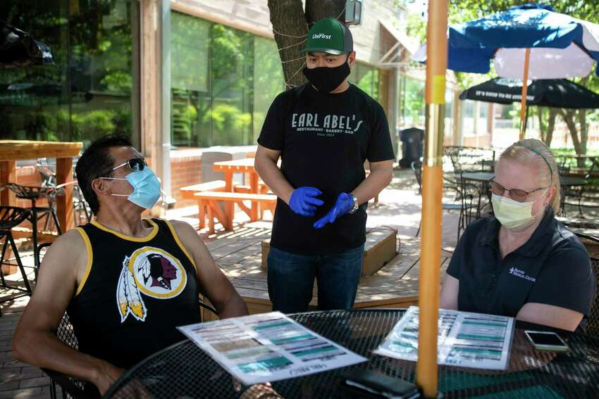Danny Badiola takes orders from the first customers Ed and Laura Nasis at Earl Abel's on May 1. Earl Abel's is reopening for patio-only table service following restrictions on restaurants being lifted by Gov. Greg Abbott.