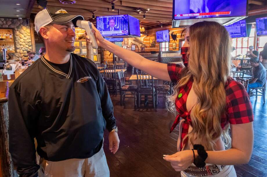Katelyn Schall takes the temperature of patron Vince Rinando as he comes into Twin Peaks on the first day of business reopening. Photo made on May 1, 2020. Fran Ruchalski/The Enterprise Photo: Fran Ruchalski/The Enterprise / © 2020 The Beaumont Enterprise