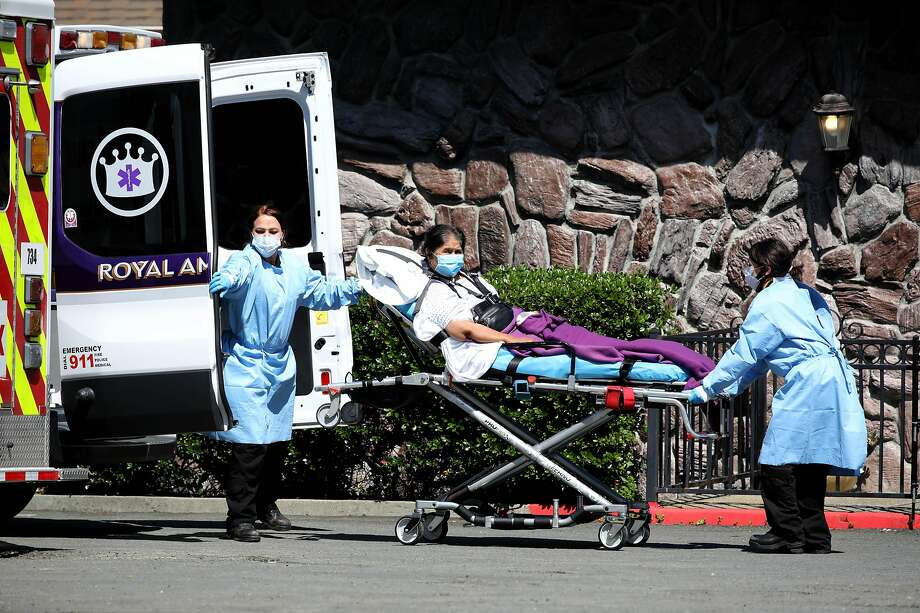 Emergency medical technicians with Royal Ambulance unload a patient at Gateway Care & Rehabilitation Center in Hayward, which has seen a deadly outbreak of the coronavirus. Photo: Yalonda M. James / The Chronicle