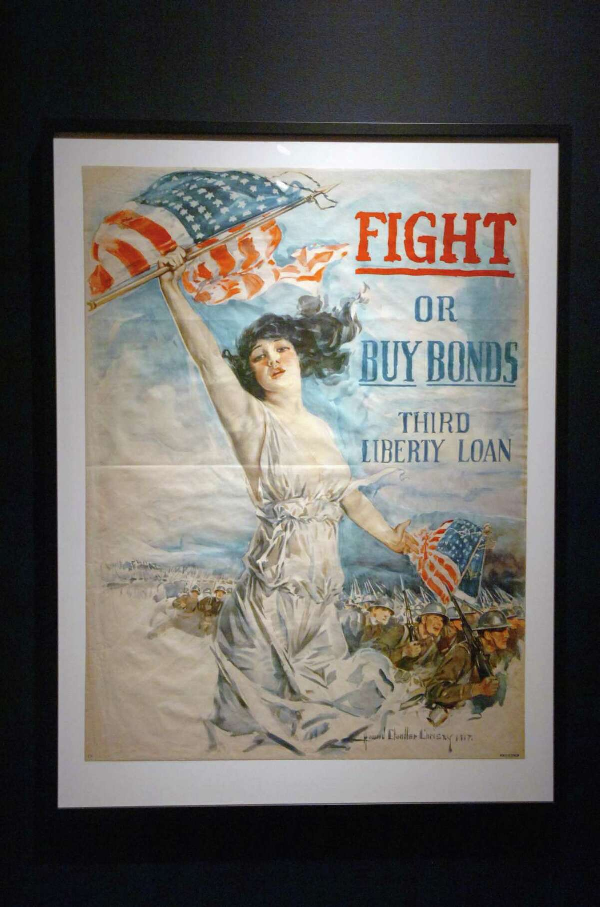 """110708--Bruce Museum--Greenwich--Artist Howard Chandler Christy's """"Fight or Buy Bonds"""" shows Columbia, who personified America, waving the flag. The Bruce Museum's new exhibit """"That Liberty Shall Not Perish: World War I Posters"""" which features seventeen original posters now nearly 200 years-old. The posters are a gift to the Museum's permanent collection by Beverly and John Watling. Keelin Daly/ Staff Photo"""