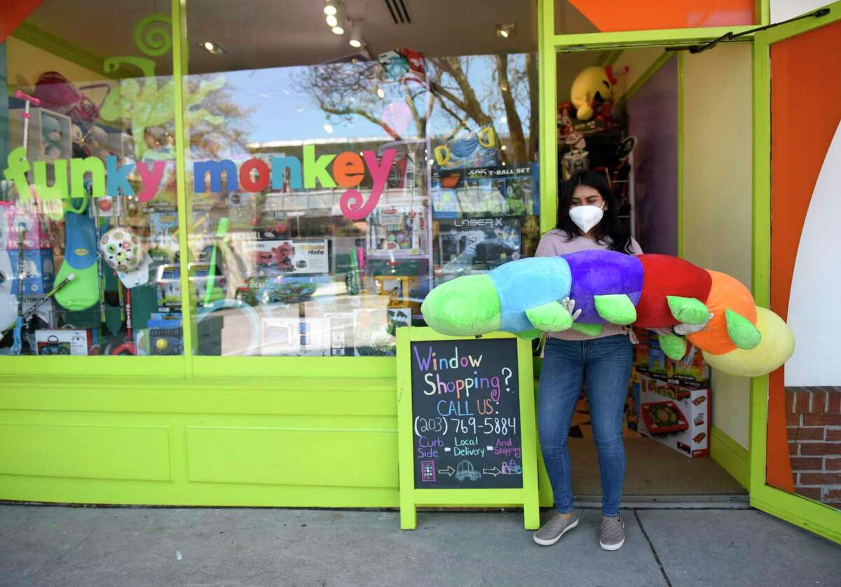 Brand Associate Gabriela Llanos brings out a giant stuffed caterpillar from the Funky Monkey toy store at 86 Greenwich Ave., in downtown Greenwich, Conn., on Tuesday, April 28, 2020. Funky Monkey offers curbside pickup for orders as a way to safely socially distance during the coronavirus pandemic.
