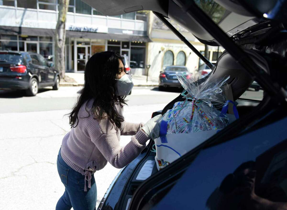 Brand Associate Gabriela Llanos takes a customer's order to their car outside Funky Monkey in Greenwich, Conn., on Tuesday, April 28, 2020. Funky Monkey offers curbside pickup for orders as a way to safely socially distance during the coronavirus pandemic.