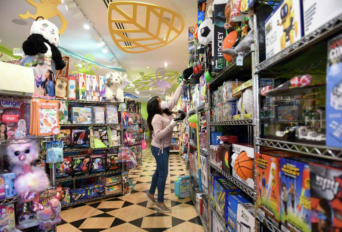 Brand Associate Gabriela Llanos takes items off the shelves at Funky Monkey in Greenwich, Conn., on Tuesday, April 28, 2020. Funky Monkey offers curbside pickup for orders as a way to safely socially distance during the coronavirus pandemic.