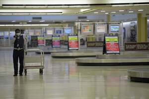 An American Airlines worker walks in a deserted baggage claim area at Reagan National Airport in Arlington on Friday. (