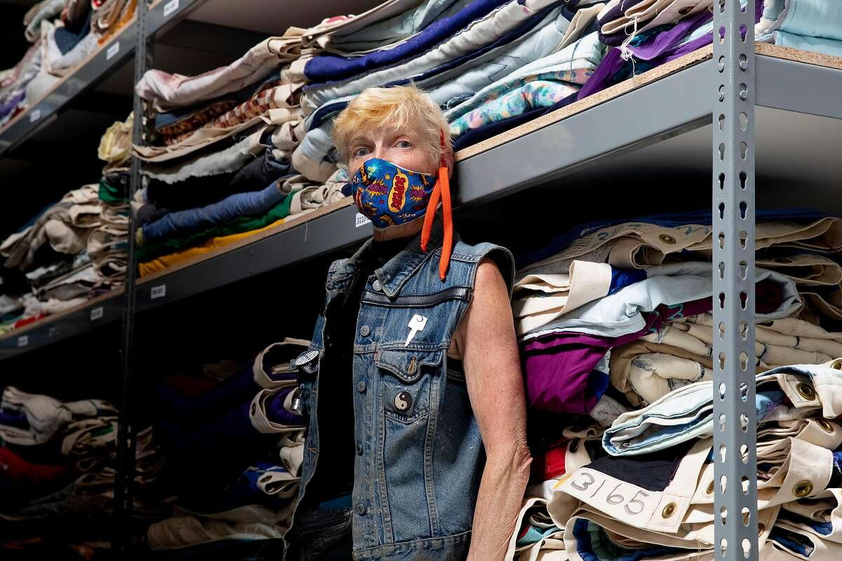 Gert McMullin sports a face mask she made while posing for a portrait among shelves filled with panels from the famed AIDS quilt at their warehouse in San Leandro, Calif. Friday, May 1, 2020. McMullin was one of the founders of the AIDS quilt, sewing two of the first panels to memorialize friends who died in the early 1980s. Now that the second plague of her lifetime has hit, she's using that leftover fabric to sew masks for nurses, the homeless and others in need.