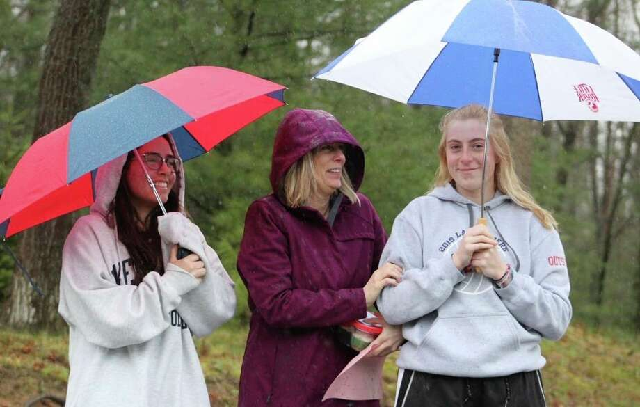 Manistee Catholic Central senior Rylee Feliczak (right) and her family stand at the end of their driveway watching the Decision Day parade of Saber supporters and emergency personnel drive by on Wednesday. (Courtesy photo)