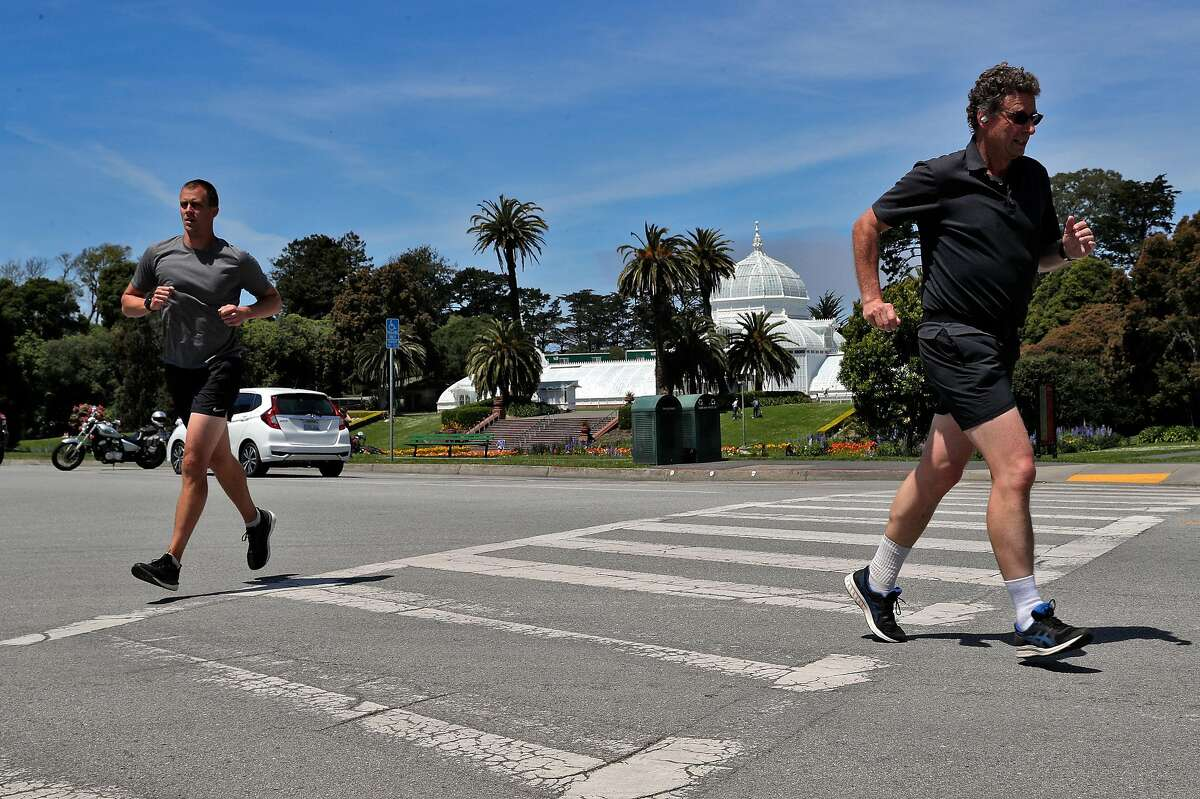 Two joggers make their way on John F. Kennedy Drive in Golden Gate Park in San Francisco, Calif., on Monday, April 27, 2020. City health officials extended the stay at home order until the end of May, and will be shutting down the street to vehicle traffic.
