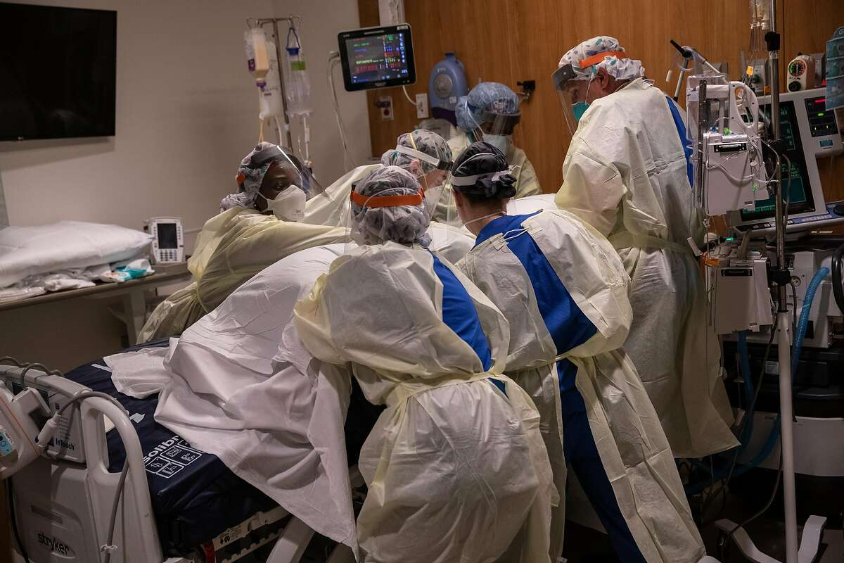 """A """"prone team,"""" wearing personal protective equipment (PPE), turns a COVID-19 patient onto his stomach in a Stamford Hospital intensive care unit (ICU), on April 24, 2020 in Stamford, Connecticut."""