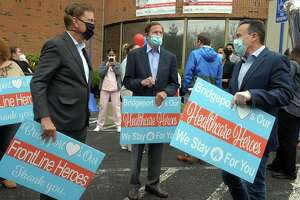 Gov. Ned Lamont, left, U.S. Sen Richard Blumenthal, center, and Mayor Joe Ganim speak together during a thank you rally in front of Northbridge Health Care Center in Bridgeport May 1, 2020. State and local rules on reopening Connecticut are being formulated.