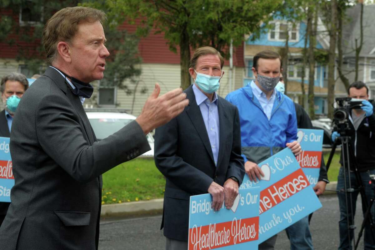 Gov. Ned Lamont, without a mask, is joined by U.S. Sens. Chris Murphy, right, and Richard Blumenthal, in a May file photo.