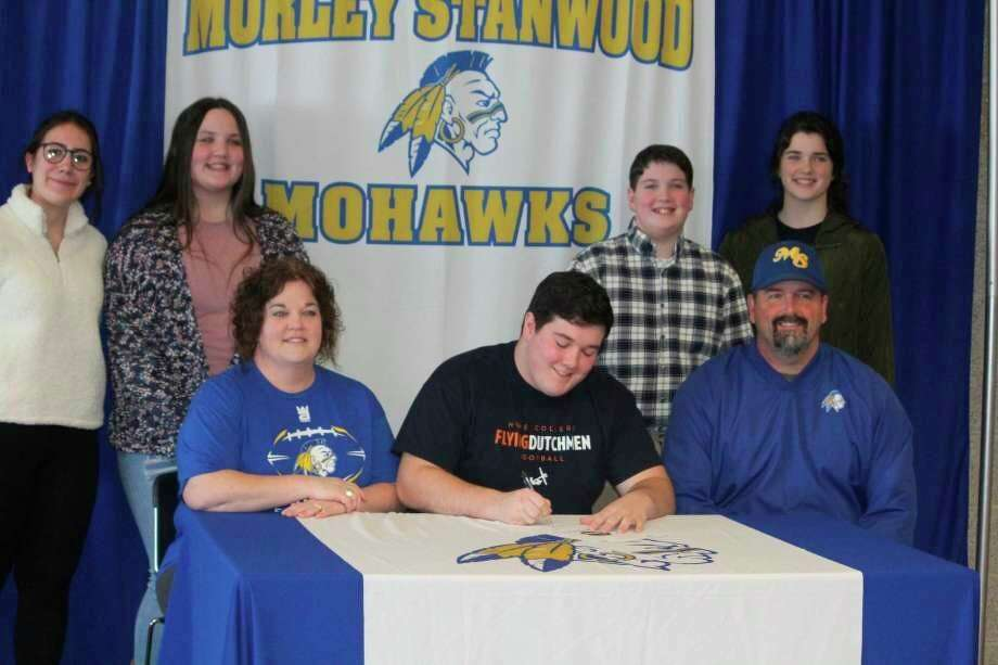 Logan Griffes, sitting next to his parents, Mike and Erin Griffes, signs a letter of intent to play at Hope. Family members in back are his foreign exchange student (from left)sister Viola Orsi, sister Molly Griffes, brother Luke Griffes and sister Morgan Griffes. (Pioneer file photo/John Raffel)