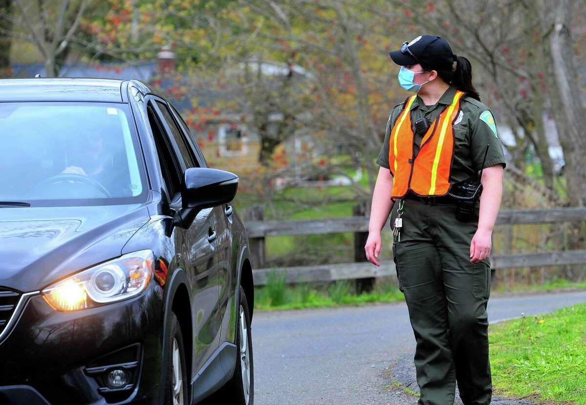 Park ranger Gina Gambino checks for a resident sticker at the entrance to Twin Brooks Park in Trumbull, Conn., on Friday May 1, 2020, the first day Twin Brooks and Old Mine Park reopened. Playgrounds, rest rooms, athletic fields and pavilions remain closed.