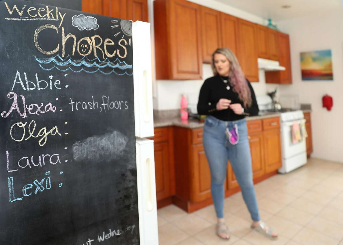 Alexa Lewis has been living alone when room mates have moved elsewhere since the stay-at-home order on Thursday, April 30, 2020, in San Francisco, Calif. House chores of the recent past tenants are seen on a chalkboard seen on the side of the refrigerator at left.